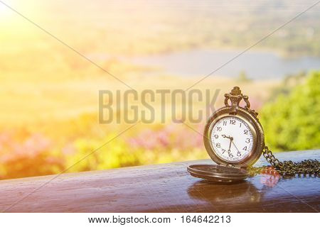 watch locket on the wooden table and flare