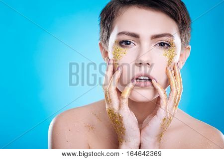 Just believe me. Pleasant woman holding her hands on the face while posing against blue background