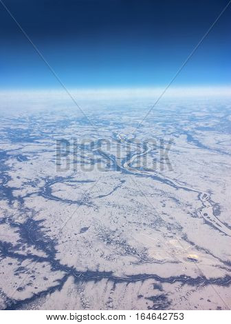 Aerial view of Northern Canada taken from flight over the vast expanse of frozen rivers and snowy landscape