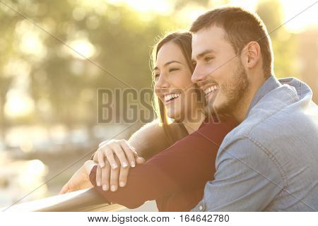 Enamored couple embracing and looking away enjoying views at sunset in a balcony with a warm light in the background