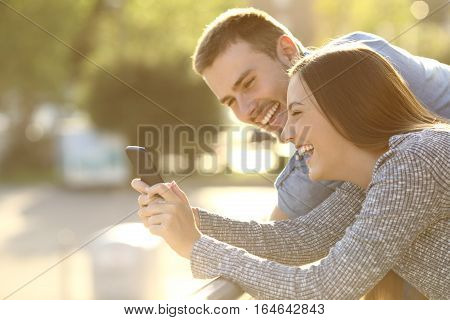 Side view of a couple laughing watching media content in a smart phone outdoors in a balcony at sunset with a warm light