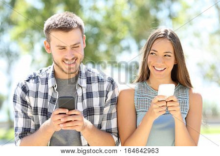 Front view of two friends flirting everyone with a smart phone and looking each other in a first date in a park with a green background