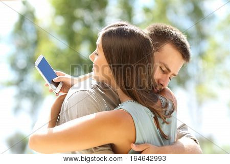 Girlfriend cheating texting on the phone and hugging her innocent boyfriend