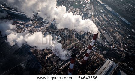 Air pollution by smoke coming out of two factory chimneys. Industrial zone in the city. Kiev, Ukraine, aerial view