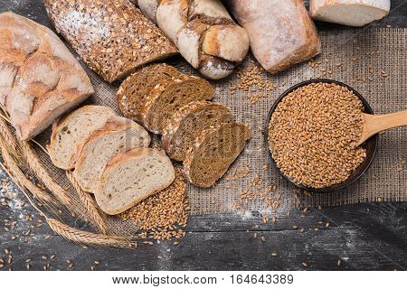 Plenty of sliced bread background. Bakery and grocery concept. Fresh, healthy whole grain sliced sorts of rye and white loaves, sprinkled flour on sackcloth and rustic wood table, food top view