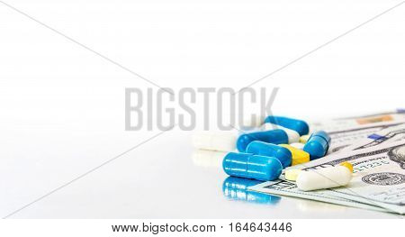 Pills with money on reflective background .