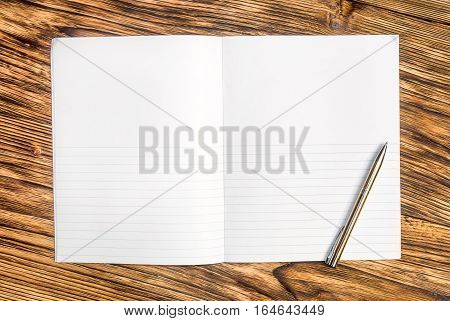 Copybook with pen on the table top.