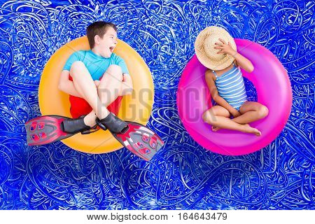 Raucous little boy and his quiet young sister relaxing together on bright colorful plastic rings in the swimming pool enjoying a hot summer day conceptual image on blue painted water background with ripples
