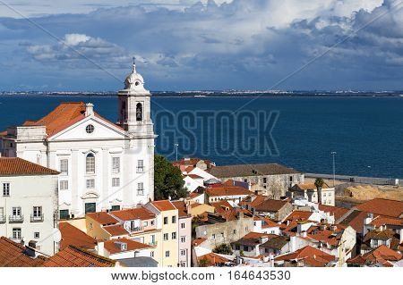 View of the Alfama Neighbourhood in Lisbon with the Tagus River in the background in Portugal