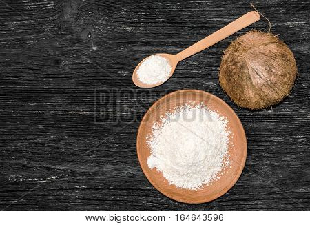 Coconut with desiccated coconut in a bowl and spoon on the table.