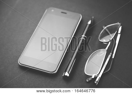 black smart phone with pen and glasses