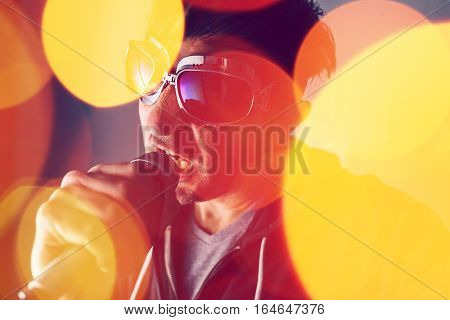 Alternative rock music singer singing song into microphone bokeh light effect and selective focus