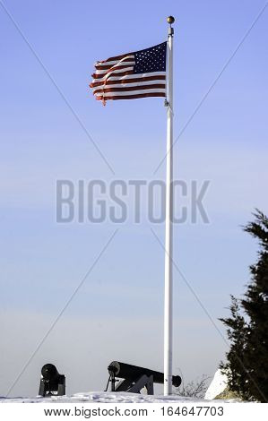 Frayed American flag in stiff breeze over cannon at Fort Phoenix in Fairhaven Massachusetts