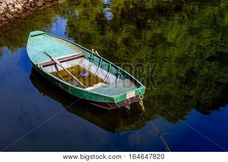 With a rope moored green painted rowboat with a shallow layer of water an oar and a bucket. The rowboat is situated on the edge of a Dutch river with a mirror smooth reflecting water surface.