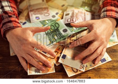 Greedy hands withdrawing pile of euro banknotes cash money on office desk