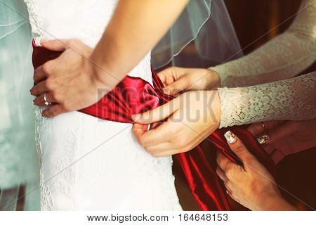 Women's hands adjust a red satin belt on bride's waist