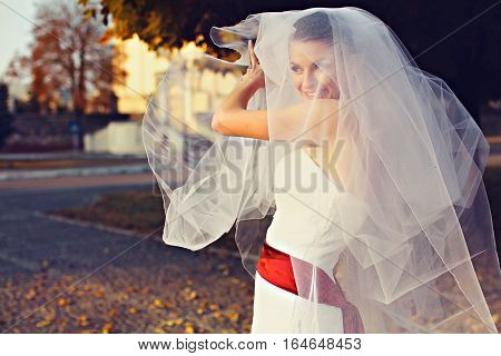 Smiling Bride Plays With A Veil In The Rays Of Evening Sun