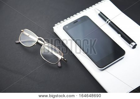 black smart phone with notebook and pen with copy space