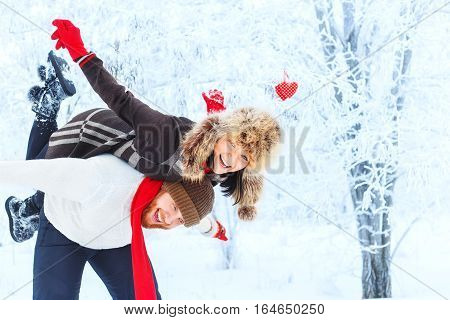 Happy winter couple. Man giving woman piggyback ride on winter vacation in snowy forest. Winter fun couple playful together outdoor. Valentine's Day and love concept