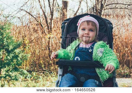 portrait of a smiling little baby with blue eyes in a pink hat and green jacket tinted photo
