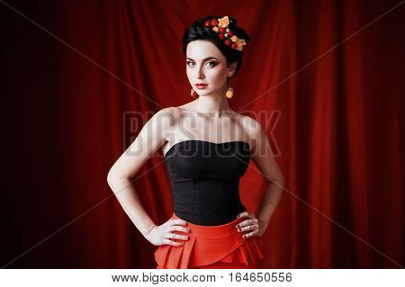 a beautiful girl brunette woman with brown eyes with bright makeup make-up with berries and flowers in hair red lips unusual appearance a woman with tanned skin on red dark background