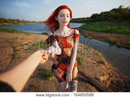 beautiful red-haired girl in sundress standing on the background of the river sunny summer day a woman with an unusual appearance with pale skin european hold the hand