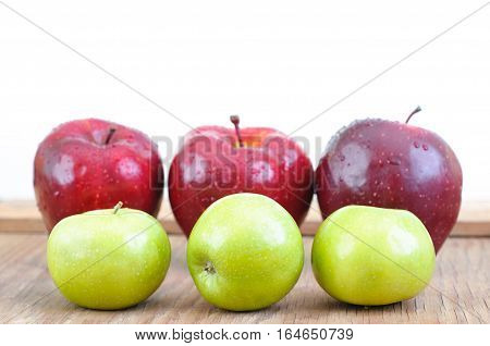 green and big red apples on wooden table