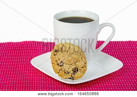 oatmeal and raisin cookie with black coffee in white cup and square saucer on bright pink place mat