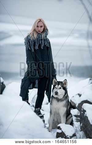 Girl with dog Malamute among rocks in winter. She stands on snow among rocks. Dog sits next to girl.