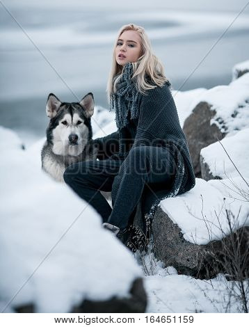 Girl with dog Malamute among rocks in winter. They sit on rocks among stones and snow.