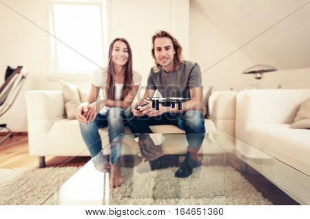 Young couple playing with a small quadrocopter drone at home in their living room.