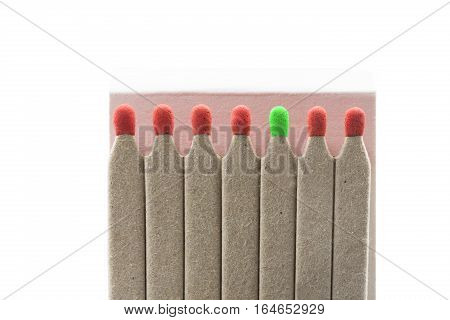 Matches with red and one green heads isolated on white background