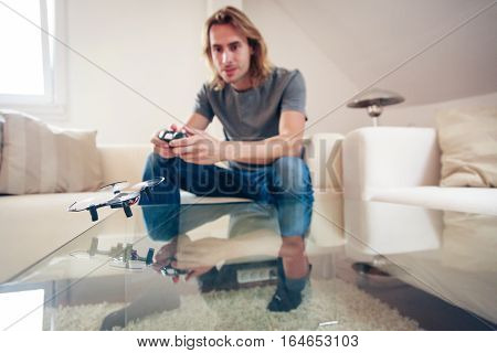 Young man playing with a small quadrocopter drone at home in his living room.