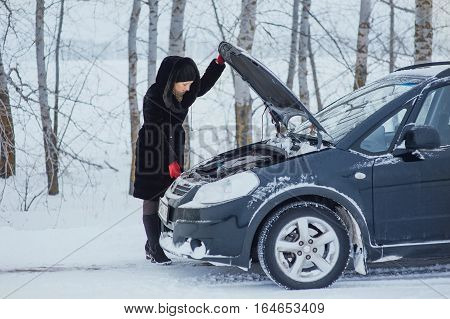 Beautiful girl repairing the car on winter road
