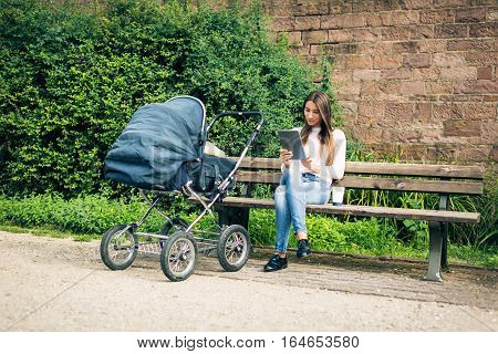Young mother enjoying time outdoors and reading on tablet, taking the baby to a park along the banks of the river Neckar in Heidelberg, Germany.