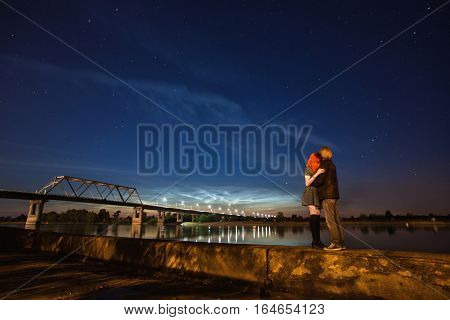 beautiful night scenery the stars in the night sky a couple on a background of the night sky red-haired girl and a guy noctilucent clouds on the horizon surface of water bridge over the river