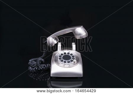 Metal, shiny retro telephone on a black background