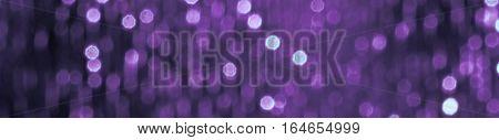 Glitter sparkling abstract purple bokeh defocused background, border design panoramic banner