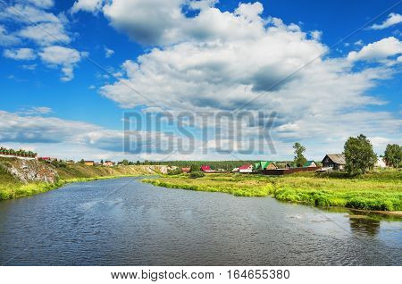 Beautiful summer rural landscape with river and clouds on the blue sky. Russia. Ural. Village Sloboda