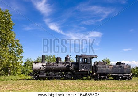 Dramatic view of an old steam train engine. Abandoned locomotive and coal car seen on the prairie with copy space in blue sky if needed.