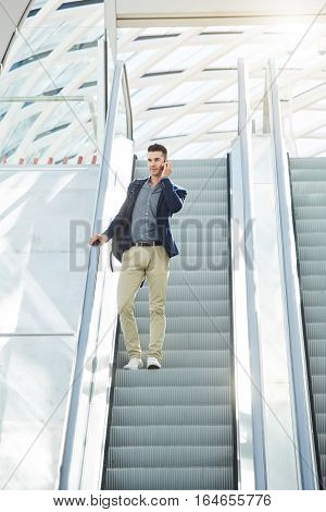 Business Man Standing On Escalator With Mobile Phone