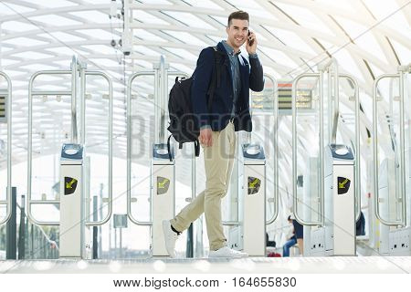 Smiling Business Man By Turnstile On Phone Call