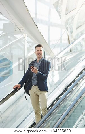 Handsome Business Man On Escalator Smiling With Smart Phone