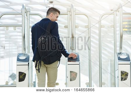 Rear portrait of business man at automated turnstile with cellphone