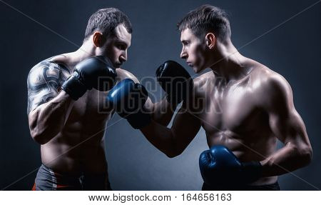 Two boxer with boxing gloves before a fight on a black background
