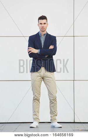Staring Young Business Man Standing With Arms Crossed