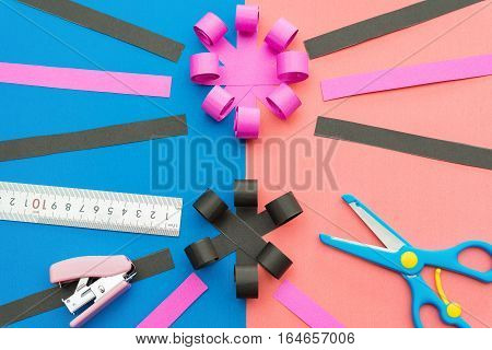 hand made flower with ruler pen scissors and stapler on colorful scrapbook
