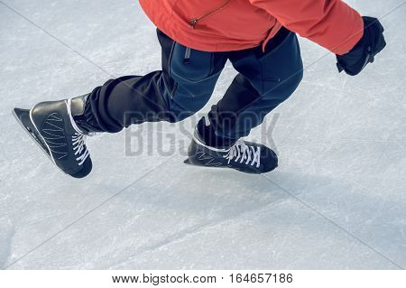 Close-up of ice skater's feet on ice rink