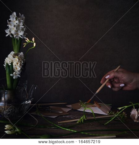 three white hyacinth in transparent vases, a female hand with a brush on a dark background.