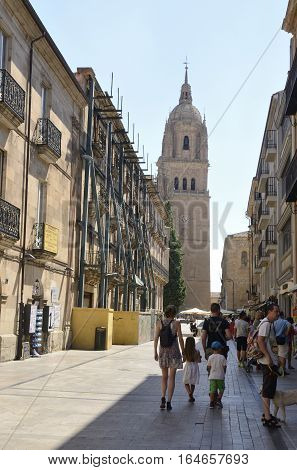 SALAMANCA, SPAIN - AUGUST 3, 2016: People at a street that ends at the Bell Tower of the New Cathedral in Salamanca Spain.